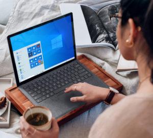 Eine Frau nutzt Remote Work und hat ihren Laptop im Bett auf einem Tablett mit Füßen. Bild: Unsplash/Windows